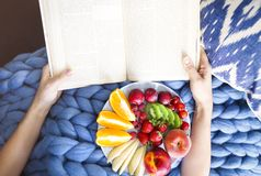 Plate with fresh fruit salad on a blue plaid and book. Woman rea. Ding the book and eating fresh fruits. Close up. Top veiw. Cozy and healthy concept Royalty Free Stock Images