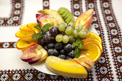 Plate with fresh fruits for the holidays: banana, grapes, orange, apple, kiwi, mint Stock Photography