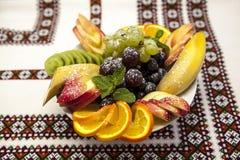 Plate with fresh fruits for the holidays: banana, grapes, orange, apple, kiwi, mint Stock Photo