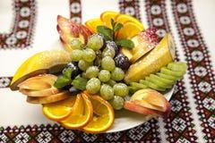Plate with fresh fruits for the holidays: banana, grapes, orange, apple, kiwi, mint Royalty Free Stock Photos