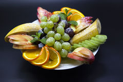 Plate with fresh fruits for the holidays: banana, grapes, orange, apple, kiwi, mint Stock Images