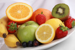 Plate with fresh fruits. Such as oranges, apples, bananas and strawberries stock images