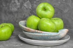 Plate with fresh green apples. On table Royalty Free Stock Images