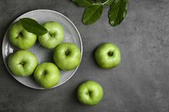 Plate with fresh green apples. On table Royalty Free Stock Photos