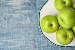 Plate with fresh green apples on wooden background. Top view Royalty Free Stock Images