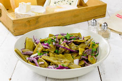 Plate of fresh green beans and red onions Stock Photography