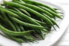Plate with fresh green French beans on table. Closeup stock image