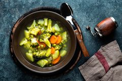 Plate of fresh hot vegetable soup with broccoli. Potato, green peas, onion and carrot. healthy vegan diet food, top view Royalty Free Stock Photography