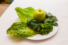 Plate of fresh mixed green salad and apple on wooden table close up. Royalty Free Stock Photos