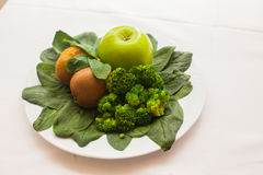 Plate of fresh mixed green salad and apple on wooden table close up. Royalty Free Stock Photography
