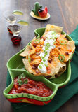 Plate of fresh nachos with  cheese. Fresh cheese nacho with vegetable on the top Royalty Free Stock Photo
