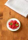 Plate of fresh raspberries. On wooden table Royalty Free Stock Photo