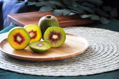 Plate of Fresh Red Kiwifruit on Table. Wooden plate of fresh red kiwifruit put on table stock photos