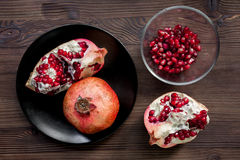 Plate of fresh red pomegranate sliced fruit with seeds wooden background top view Stock Photos
