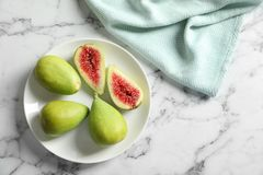Plate with fresh ripe figs on marble background. Top view stock photography