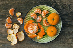 A plate of fresh ripe juicy mandarins over a rough wood backgrou Stock Image