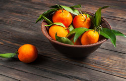 Plate of fresh ripe juicy mandarins over a rough wood background Royalty Free Stock Images