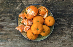 Plate of fresh ripe juicy mandarins over a rough wood background Stock Photos