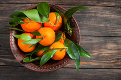 Plate of fresh ripe juicy mandarins over a rough wood background. Top view Royalty Free Stock Photography