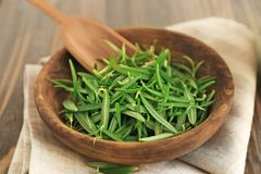 Plate with fresh rosemary leaves. On table Stock Images