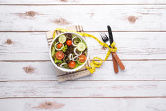 Plate with fresh salad, measure tape, cup, knife and fork. Diet Stock Photography