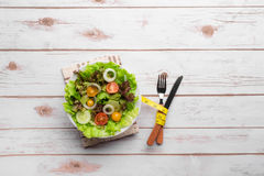 Plate with fresh salad, measure tape, knife and fork. Diet Stock Photos