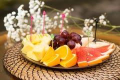 Plate with fresh sliced fruits. Banana, grapes. grapefruit, orange Stock Photos