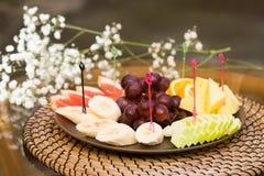 Plate with fresh sliced fruits. Banana, grapes. grapefruit, orange Royalty Free Stock Images
