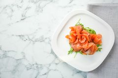 Plate with fresh sliced salmon fillet and arugula. On marble background, top view royalty free stock image