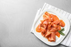 Plate with fresh sliced salmon fillet and rosemary. On gray background, top view stock image