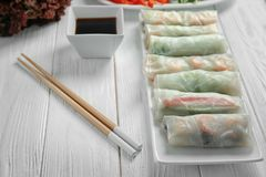 Plate with fresh spring rolls in rice paper. On wooden table Stock Images