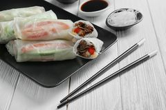 Plate with fresh spring rolls in rice paper. On wooden table Royalty Free Stock Photography