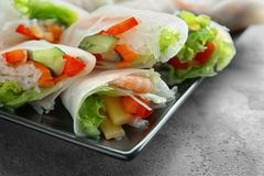 Plate with fresh spring rolls in rice paper. On table Stock Image