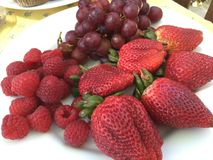 Plate of fresh strawberries, grapes and raspberries Stock Image