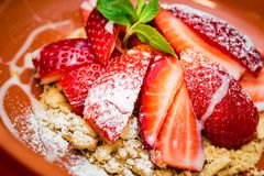 Close up strawberry dessert with cookie crumbles. Plate with fresh strawberry and cookie crumbles served in restaurant. Selective focus stock images