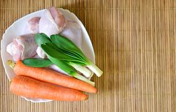 Plate with fresh vegetables and raw chicken legs. Ingredients for cooking: chicken, carrots, green onions Stock Photography