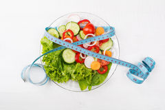 Plate with fresh vegetables salad and measured tape isolated on Royalty Free Stock Image
