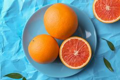 Plate with fresh yummy oranges. On color paper  background Royalty Free Stock Image