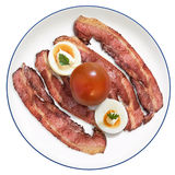 Fried Bacon Rashers With Hard Boiled Garnished Egg Slices And Tomato Set On White Porcelain Plate Isolated On White Background Stock Photos