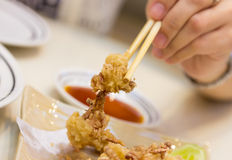Plate of fried calamari served and chopstick with hand Royalty Free Stock Photos