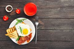 Plate with fried egg, bacon and toasts stock photo