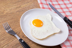 Plate with fried egg, fork and knife on the table Stock Photos