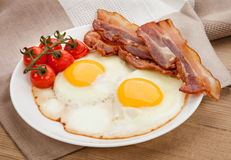 Plate with fried eggs, bacon on board Royalty Free Stock Image