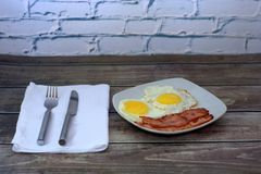 A plate with fried eggs, bacon and croutons stands on the table next to a napkin with a knife and fork. Close-up. A plate with fried eggs, bacon and croutons royalty free stock images