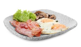 Plate with fried eggs, bacon, mushrooms. And lettuce on white background stock images