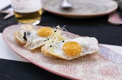 Plate of fried eggs on mini crispy toast with truffle royalty free stock photo