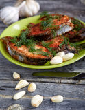 Plate with fried fish and garlic on a  table Stock Photo