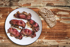 Plateful Of Fried Pork Ham Rashers With Slice Of Integral Brown Bread Set On Old Cracked Wooden Picnic Table Stock Photography
