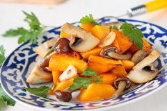 Plate of fried pumpkin and mushrooms Stock Image