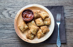 Plate with fried ravioli on the wooden board. Plate with fried ravioli and tomato sauce on the wooden board Stock Image